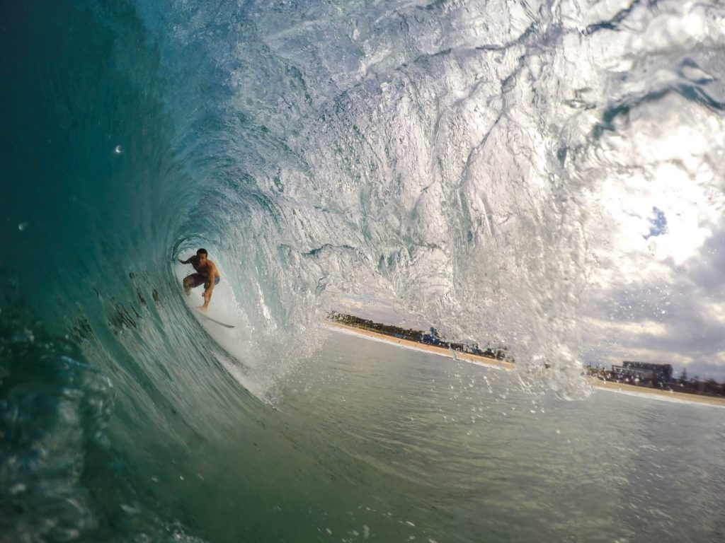 man surfing under a tall wave
